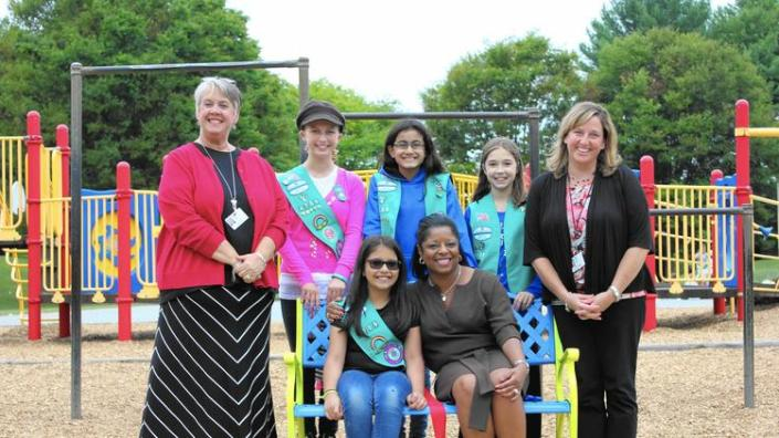 From left to right and back to front, Thunder Hill Elementary Acting Principal Martha Bowen, students Aria Lunt, Shriya Menon, and Hailey Condron, Thunder Hill Elementary counselor Rebecca Reeb, student Simran Kalia, and Howard County Public School System Chief Operating Officer Camille Jones pose after the ribbon-cutting ceremony of the Friendship Bench. (Photo by Neysa Condron)